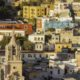 An aerial view of a cathedral and multi colored houses in Guanajuato, Mexico.